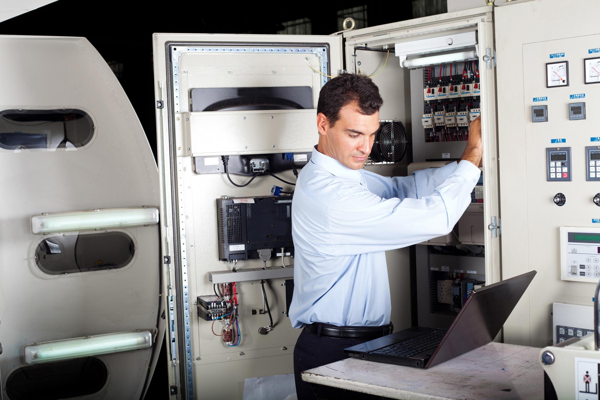 industrial technician repairing modern computerized machine in factory